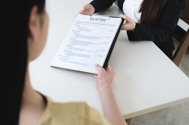 Job interview in office concept, focus on resume paper, employer reviewing good cv of prepared skilled applicant, recruiter considering application or hr manager making hiring decision