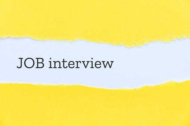 黄色い紙の背景にタイプライターで就職の面接フレーズ