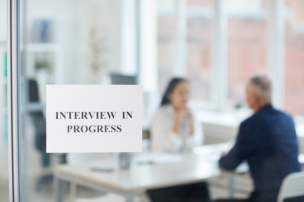 Job interview in progress sign on glass door in modern office with blurred silhouettes of two people talking, copy space