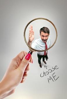 Собеседование с менеджером в офисе. концепция выбора лучшего кандидата. женская рука с лупой