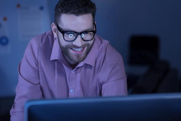 작업이 완료되었습니다. 그의 프로젝트를 마무리하고 컴퓨터 화면을 보면서 웃고 긍정적 인 행복 수염 남자