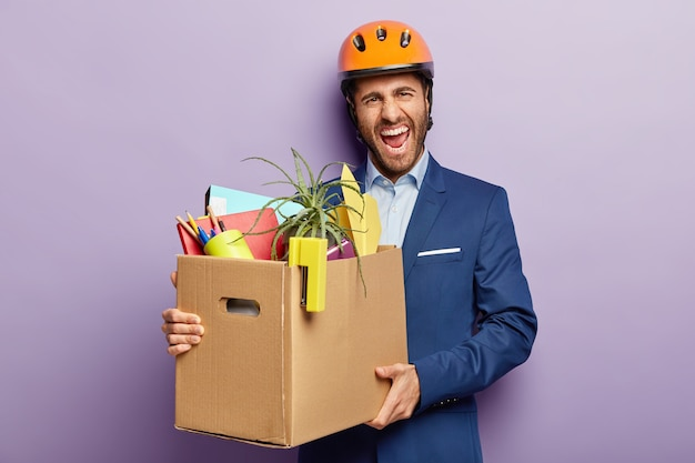 Job loss concept. annoyed male engineer fired from work, carries carton box with personal office stuff, smirks face