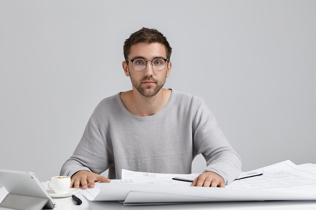 仕事、近代的な技術、創造性と職業の概念。トリミングされたひげを持つハンサムな若い男性エンジニアの写真