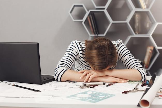 仕事と過労。長い勤務日後の頭痛に苦しんで、オフィスで手に横になっている縞模様の服で黒い髪と疲れている若い見栄えの良いエンジニア少女のクローズアップ。