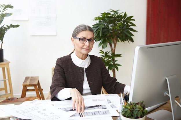 Работа, профессия, профессия и концепция карьеры. привлекательная женщина-архитектор в ее пятидесятилетнем возрасте работает на компьютере в офисе, вычисляет измерения и делает чертежи строительного проекта