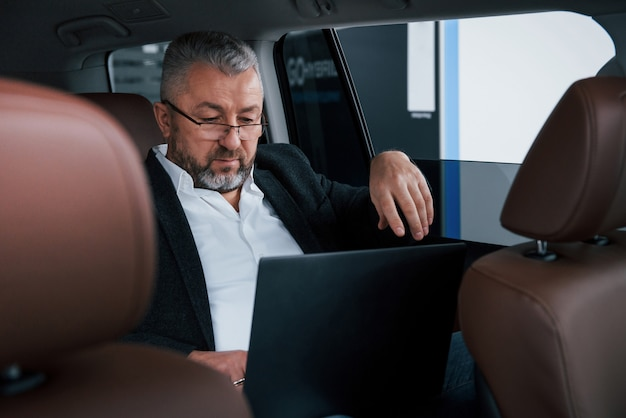Job out of the office. working on a back of car using silver colored laptop. senior businessman