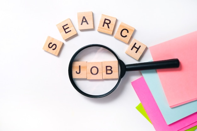 Job search concept. job search lettering on the table, many lettering sheets, magnifying glass, drawing up curriculum vitae