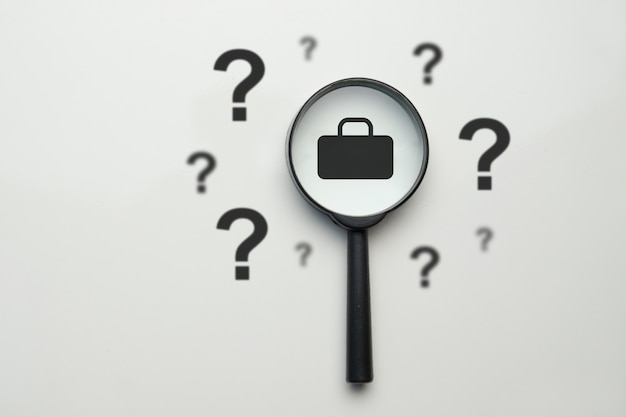 Job search concept - magnifying glass with case and question marks.