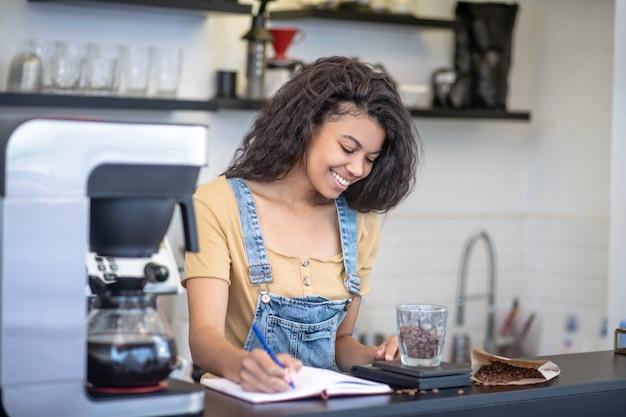 일. 커피 숍 카운터 뒤에 커피 콩의 정확한 무게를 기록하는 저울을보고 웃는 집중된 여자