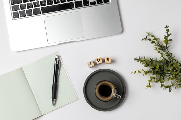 Job word on rubber stamps, coffee cup, keyboard, pen, notepad, unemployment on gray