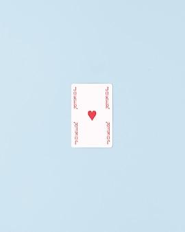 真ん中に赤いハートが1つ付いたジョッカーカード。最小限のフラットレイ構成。パステルブルーの背景。