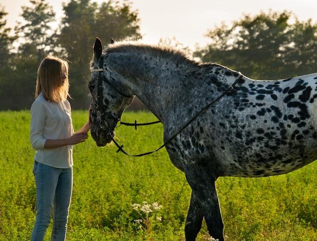 ジョッキーの女の子が開いたmanegeで馬を撫でています。かわいい騎手の女の子が彼女にキスして抱きしめている馬の近くに立っています
