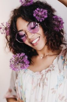 Jocund african girl posing with alliums and laughing. indoor shot of graceful black woman with wavy hair smiling.