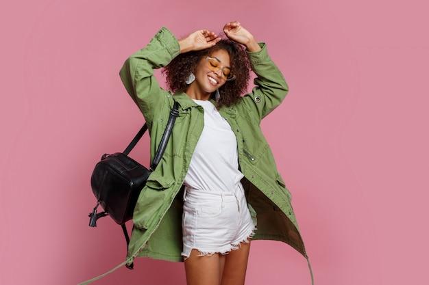 분홍색 배경에 스튜디오에서 포즈 유행 봄 재킷에 jocund 흑인 여성.
