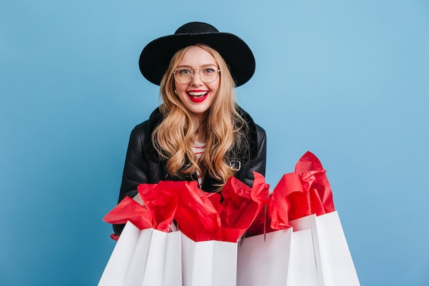 Jocund blonde woman in hat holding shopping bags. cheerful curly girl laughing on blue wall.