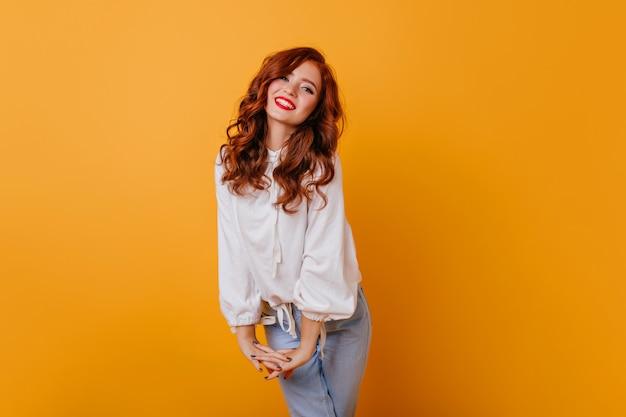 Jocund caucasin 아가씨 오렌지 벽에 웃고입니다. 우아한 흰 블라우스에 세련 된 곱슬 여자의 실내 사진.