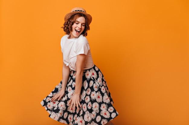 Jocund signora europea in gonna danza su sfondo giallo. affascinante ragazza in cappello di paglia che guarda l'obbiettivo con il sorriso.