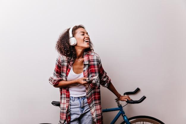 자전거 옆에 서있는 이어폰에 jocund 여성 모델. 빨간 체크 무늬 셔츠에 사랑스러운 곱슬 여자의 실내 샷.