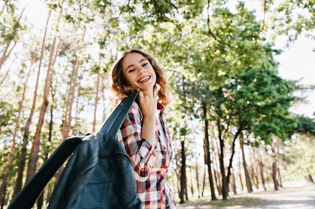 Jocund 여성 관광 자연에 재미. 배낭 화창한 날에 웃 고 사랑스러운 금발 소녀의 야외 사진.