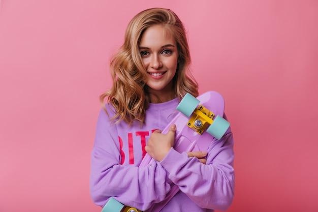 Jocund смеется женщина, держащая фиолетовый скейтборд. стильная очаровательная девушка со светлыми волосами, улыбаясь пастелью.