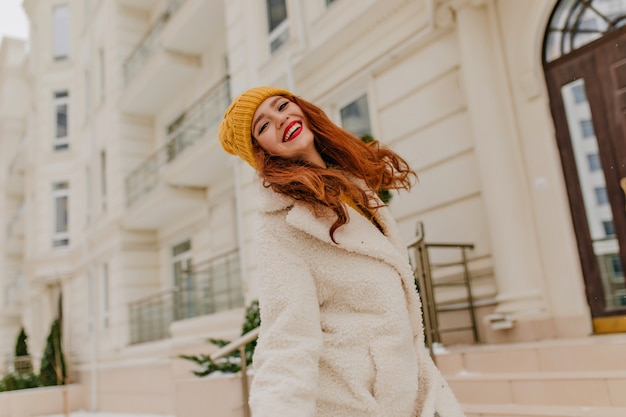 추운 날에 웃 고 모자에 jocund 긴 머리 소녀. 겨울에 야외 산책 생강 젊은 여자.