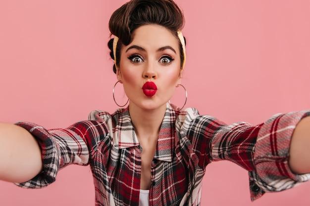 Jocund ragazza pinup in posa in camicia a scacchi rossa. donna stupita che cattura selfie con baciare l'espressione del viso.