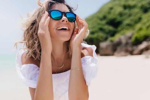 밝은 미소로 하늘을보고 여름 옷에 jocund 무두질 된 아가씨. 리조트에서 휴식을 즐기는 우아한 선글라스에 기분 좋은 여자의 야외 사진.