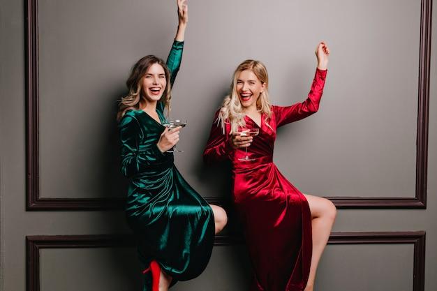 샴페인을 즐기는 빨간 벨벳 드레스에 jocund 여자. 파티에서 춤을 추는 기분 좋은 자매.