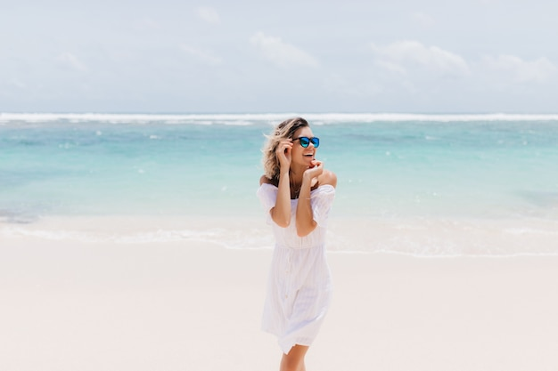 Jocund woman in romantic white attire standing on sea. laughing ecstatic woman in sunglasses spending summer day at ocean.