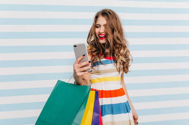 쇼핑 후 셀카를 만드는 밝은 갈색 물결 모양의 머리를 가진 jocund 여자. 꽤 웃는 소녀 재미 스트라이프 벽에 포즈.