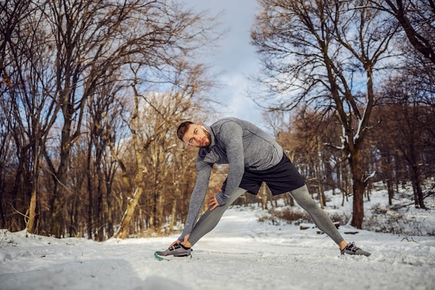 Jogger doing warm up exercises in nature at snowy winter day. winter sport, snowy weather, warm up exercises