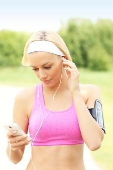 Бегун слушает музыку через смартфон в парке