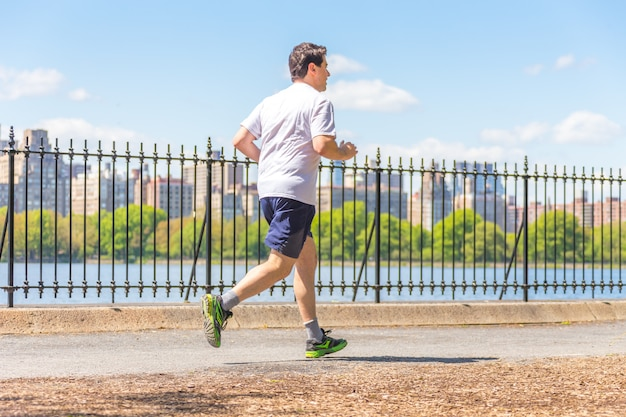 Jogger running along central park reservoir in new york. central park is full of active people throughout the year.