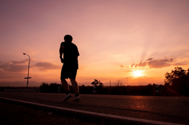 Jogger in sunset, copy space, evening sky.