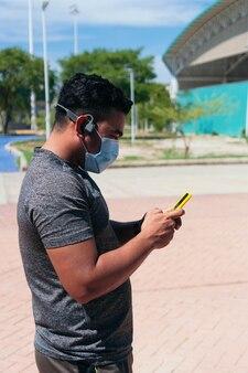 공원에서 휴대 전화를 사용하여 보호 마스크를 쓴 조깅