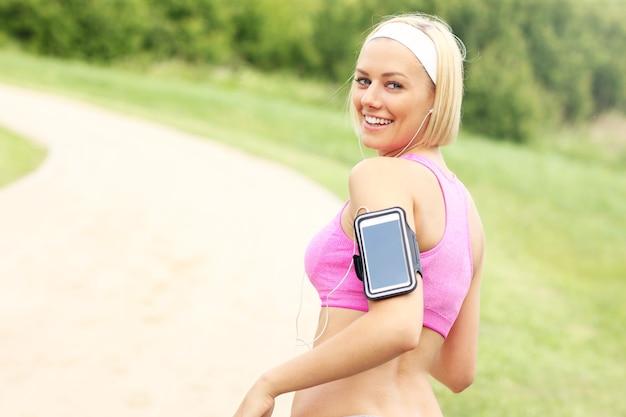 Бегун со смартфоном в парке