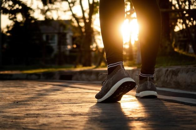ジョギングのコンセプト、ランナーの脚と足ランニングシューズを着用バックライト付きの道路から太陽までのローアングル