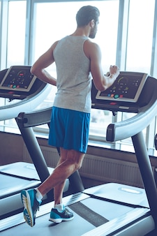 Jogging at gym. full-length rear view of young man in sportswear running on treadmill in front of window at gym