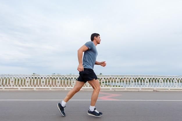ジョギングのライフスタイル-屋外で走っている若い魅力的な男性