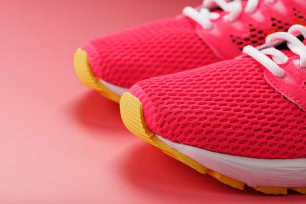 Jogging pink sneakers on a pink with free space. Premium Photo