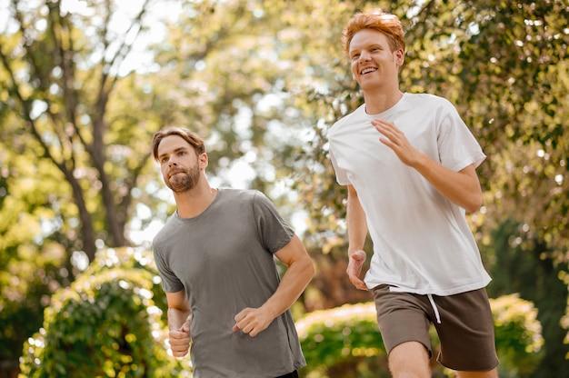 조깅. 화창한 아침에 공원에서 손을 흔들며 달리는 운동복을 입은 목적이 있는 쾌활한 빨간 머리와 검은 머리 남자