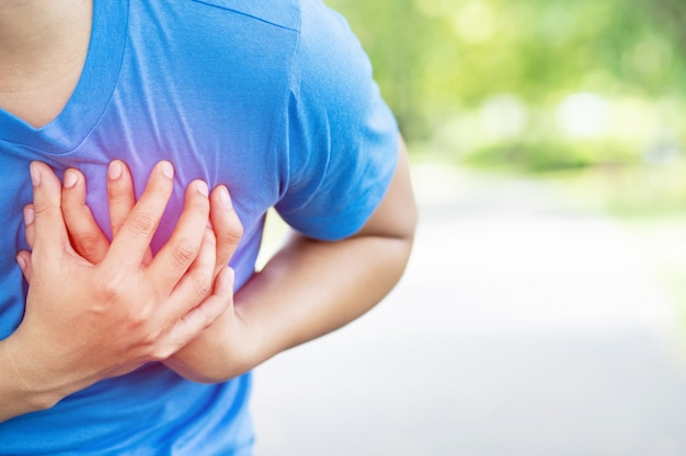 Бег трусцой бегущий человек спортсмен с болью в груди во время тренировки сердечного приступа на открытом воздухе тяжелые упражнения заставляют организм шокировать сердечные заболевания.