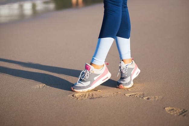 해변에서 조깅 운동화. 모래에 발자국. 운동화 소녀. 스포츠 신발.