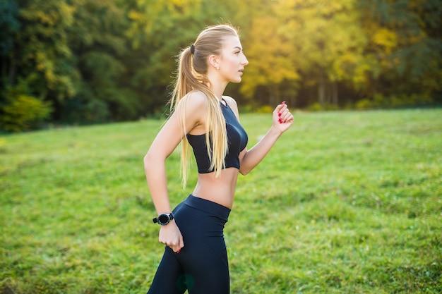 Donna che fa jogging in esecuzione nel parco sotto il sole in una bella giornata estiva. modello di fitness sportivo allenamento di etnia caucasica all'aperto per la maratona.