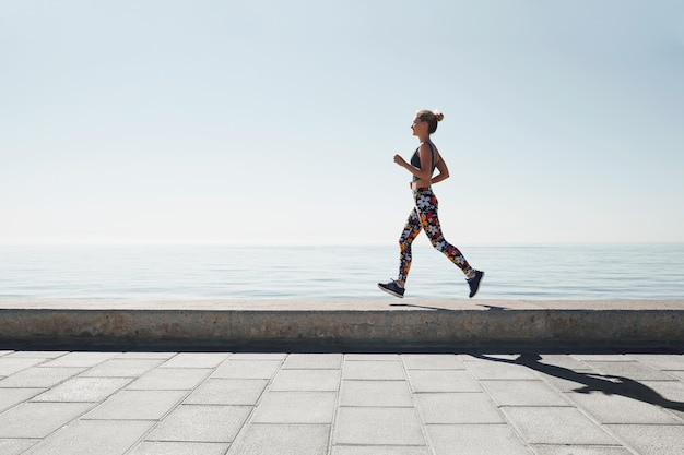 海岸を走っている若い女性のジョギング