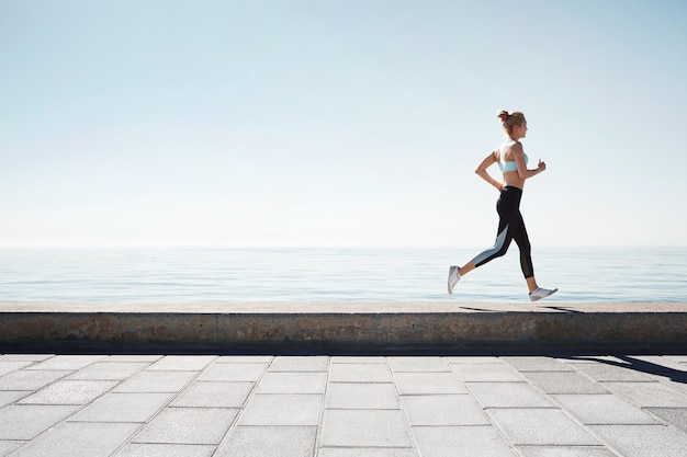Jogging young woman running on shore
