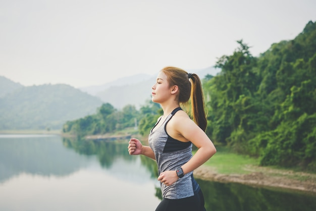 Ход молодой азиатской женщины jogging в парке на свежем воздухе и носит спорт наблюдают и проверяют ее представление.