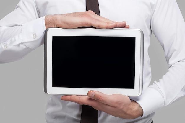 Присоединяйтесь к цифровой эпохе. обрезанное изображение мужчины в строгой одежде, держащего цифровой планшет на сером фоне
