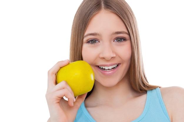 健康的なライフスタイルに参加しましょう!リンゴを持って、白で隔離されて立っている間笑顔で陽気な10代の少女