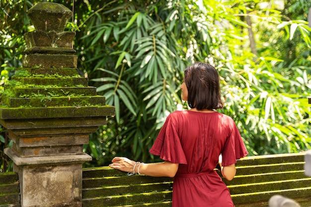 参加してください。島の熱帯の自然を楽しみながらカメラに背を向けて立っている魅力的なブルネットの女性